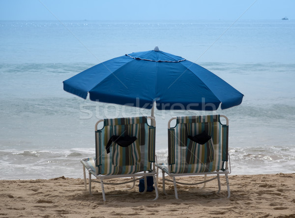 Empty beach chairs with umbrellas on sandy beach of Pacific Ocea Stock photo © tab62