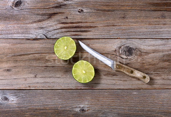 Sliced lime and paring knife on rustic wood in flat lay format Stock photo © tab62