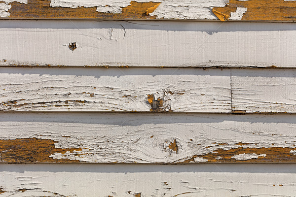 Old and fading paint peeling off of wood sliding Stock photo © tab62