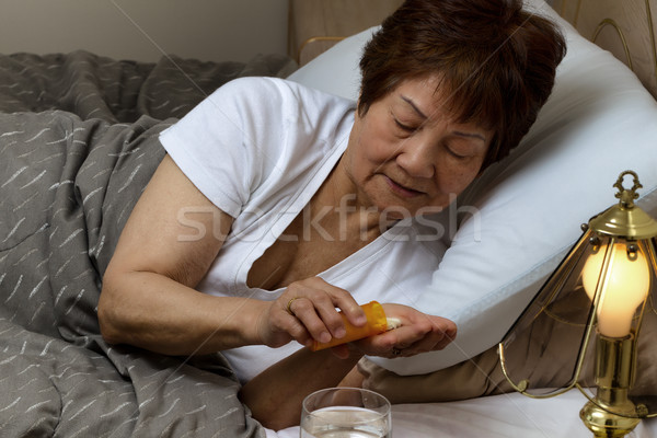 Stock photo: Senior woman taking her medicine at nighttime due to sickness