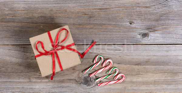 Holiday gift box and candy canes on rustic wooden boards Stock photo © tab62