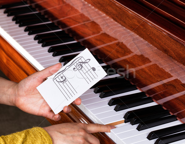 Hand holding music note to play correct key on piano keyboard  Stock photo © tab62