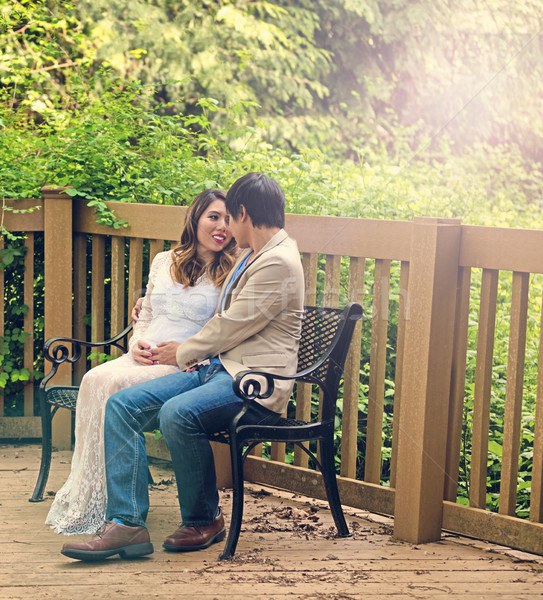 Expecting mom and dad sitting on patio bench outdoors  Stock photo © tab62
