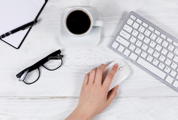 Female hand using computer mouse on organized white desktop  Stock photo © tab62