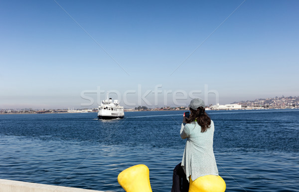 Woman taking photos of the bay of San Diego while sitting down a Stock photo © tab62