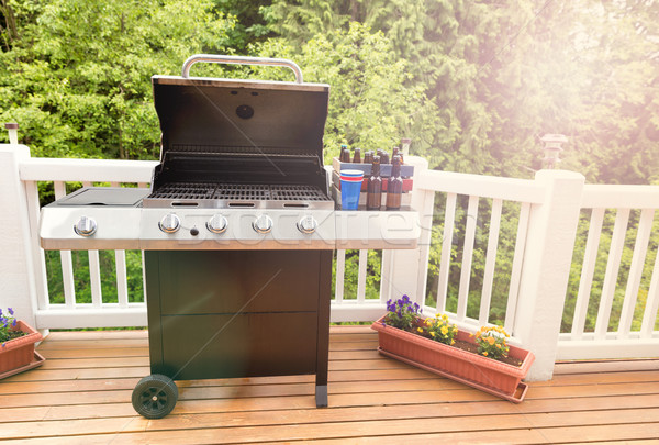 Bright daylight on deck wiht open barbecue cooker and bottled be Stock photo © tab62