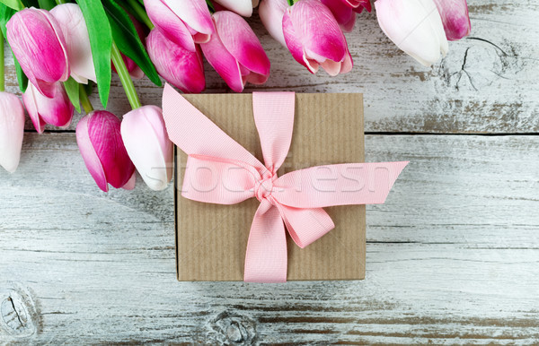 Overhead view of a brown gift box with pink springtime tulips in Stock photo © tab62
