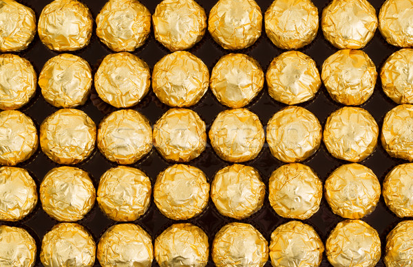 Box of candies wrapped in bright golden foil wrappers Stock photo © tab62