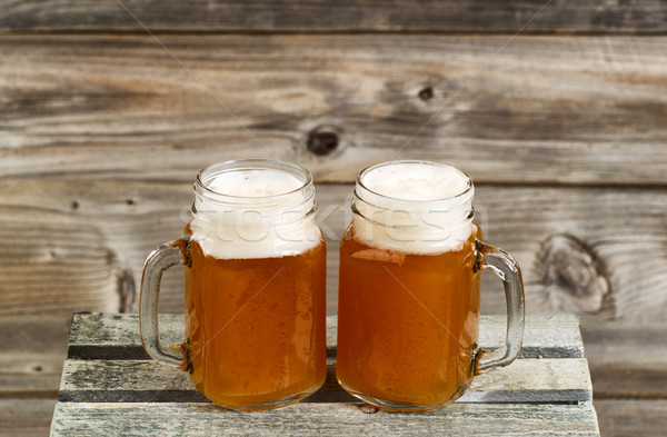 Two pints of fresh cold beer on top of wooden crate with rustic  Stock photo © tab62