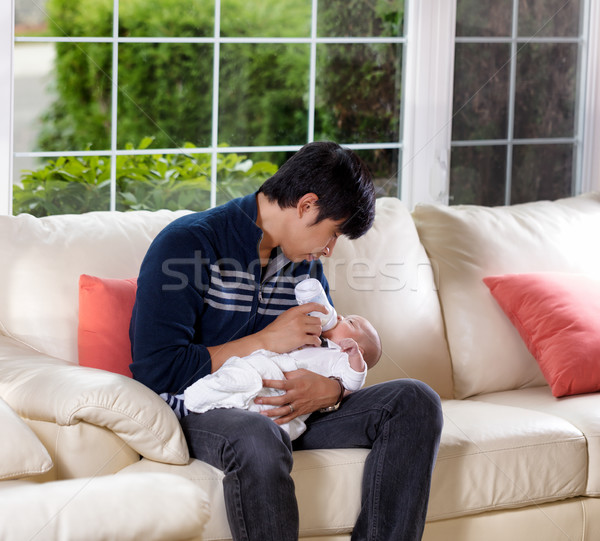 Father feeding his infant son on white sofa Stock photo © tab62