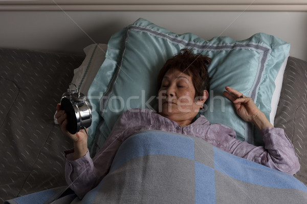 Restless senior woman looking at alarm clock during nighttime wh Stock photo © tab62