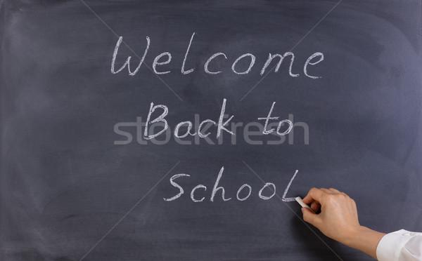 Teacher writing welcome back to school on erased black chalkboar Stock photo © tab62