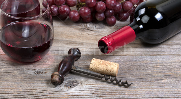 Vintage corkscrew with red wine bottle with grapes and glasses i Stock photo © tab62