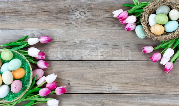 Easter eggs inside basket and bird nest with tulips on lower lef Stock photo © tab62