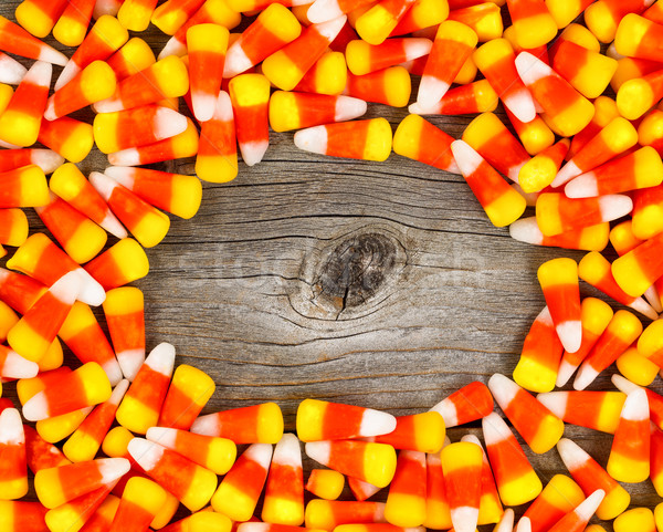 Candy corn in circle border on rustic wooden board Stock photo © tab62
