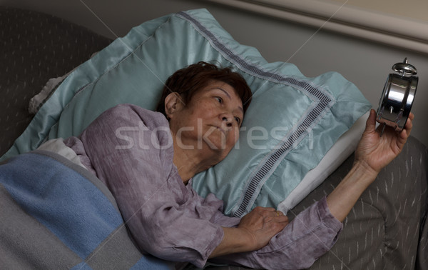 Restless senior woman glaring at alarm clock during nighttime wh Stock photo © tab62