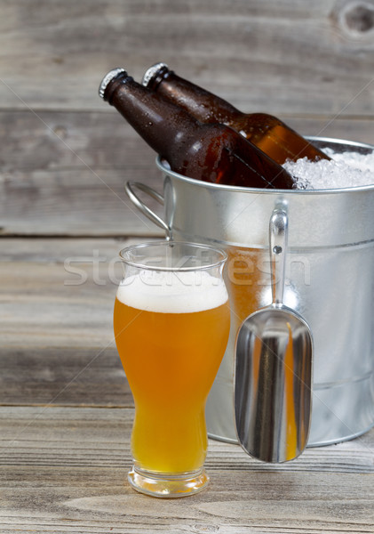 Freshly poured Beer in Glass with extra full bottles in backgrou Stock photo © tab62