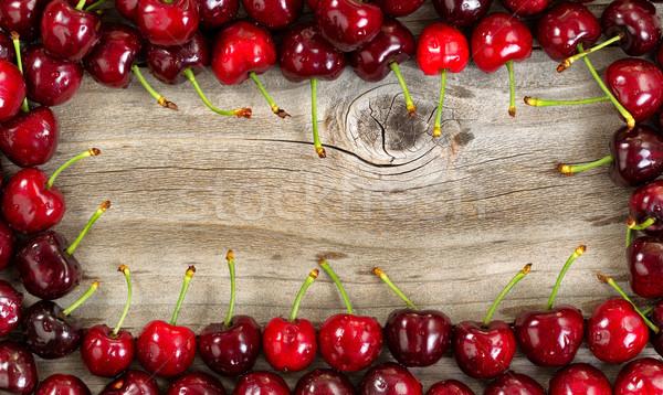 Border of black cherries on aged wood Stock photo © tab62