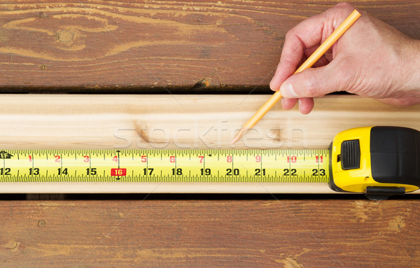 Hand measuring wooden board  Stock photo © tab62