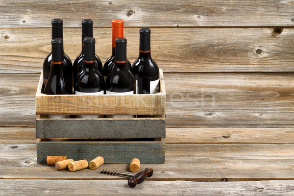 Bottles of red wine in wooden crate on rustic wooden boards Stock photo © tab62