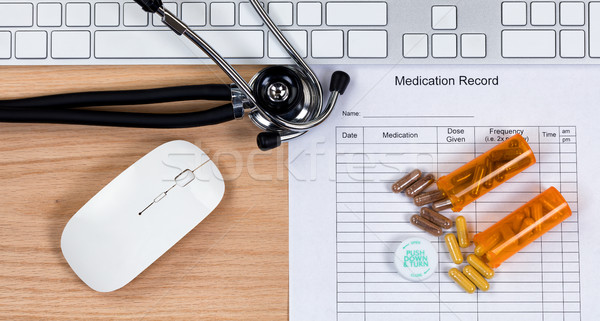 Wooden desktop with blank patient medication form plus capsules  Stock photo © tab62