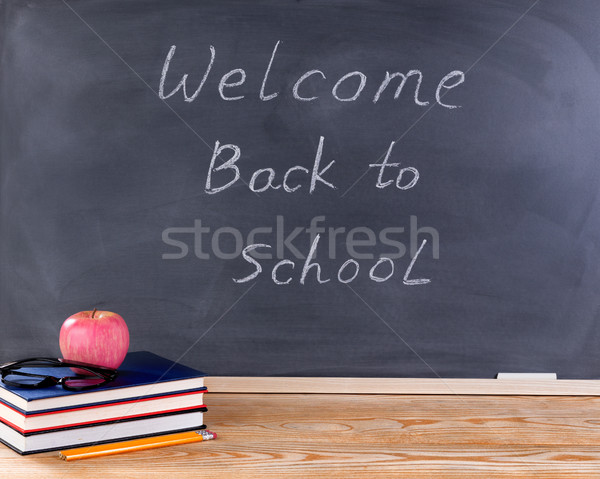 Student desktop and erased black chalkboard with welcome back to Stock photo © tab62