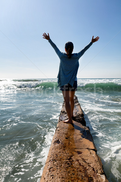 Woman walking out onto break wall with waves of ocean in front   Stock photo © tab62