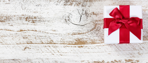 Giftbox with red bow on rustic wood in flat lay view  Stock photo © tab62