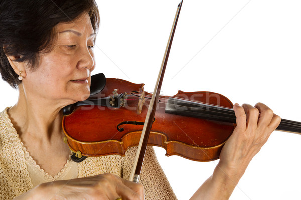 Senior woman concentrating while playing the violin  Stock photo © tab62
