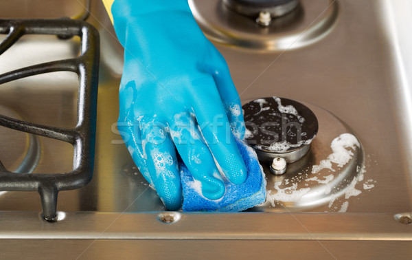 hand wearing rubber glove while cleaning stove top range with s Stock photo © tab62