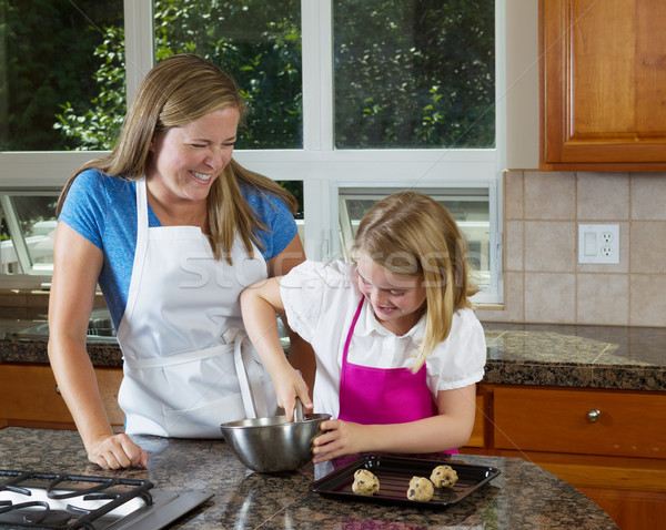 Mother watching over young daughter on how to make cookies  Stock photo © tab62