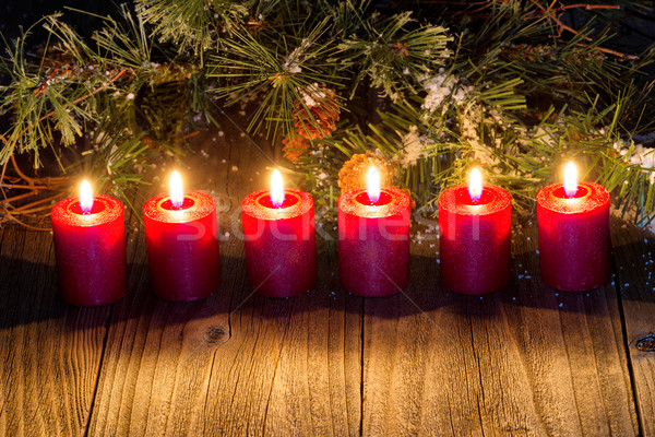 Glowing red candles with snow covered evergreen branch on rustic Stock photo © tab62