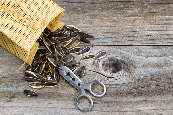 Pile of sunflower seeds with bag and opener on rustic wood  Stock photo © tab62