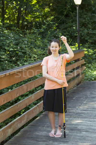 Young Girl with big smile after catching little fish  Stock photo © tab62