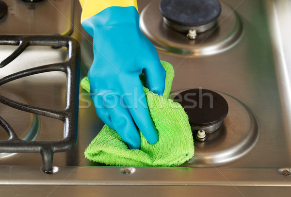 Gloved hand wiping down stove top range with green microfiber ra Stock photo © tab62