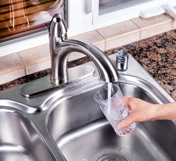 Drinking glass being filled up with tap water from kitchen fauce Stock photo © tab62