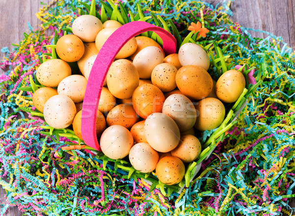 Easter eggs in basket on top of colorful Mache paper with rustic Stock photo © tab62