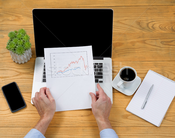Male hands holding investment graph while using laptop computer  Stock photo © tab62