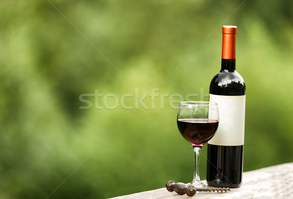 Glass of red wine and unopened bottle outdoors  Stock photo © tab62