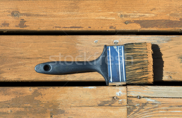 Used paintbrush filled with wood stain on a natural cedar deck Stock photo © tab62