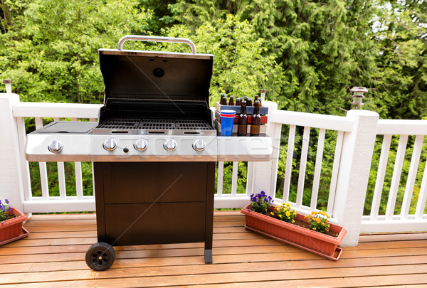 Open barbecue cooker and bottled beer on cedar wood outdoor deck Stock photo © tab62