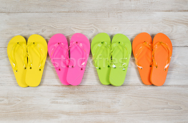 Four pairs of New Sandals on faded white wood Stock photo © tab62