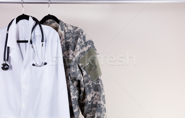 Medical white consultation coat and military uniform on hanger  Stock photo © tab62