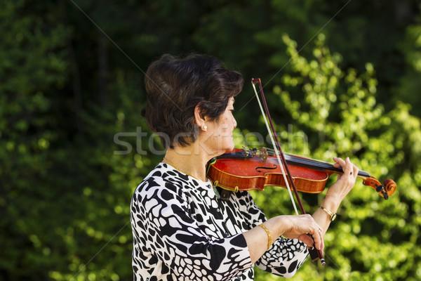 Stock photo: Senior woman playing music outdoors