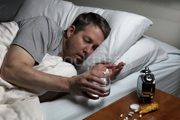 Mature man cannot fall asleep thus preparing to take medicine  Stock photo © tab62