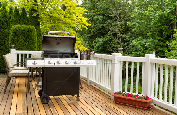 Open BBQ cooker and bottled beer on outdoor cedar patio Stock photo © tab62