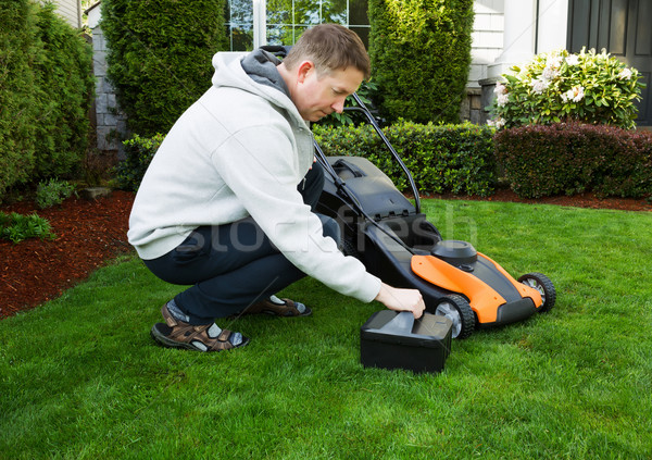 Mature man putting battery into electric Lawn Mower  Stock photo © tab62