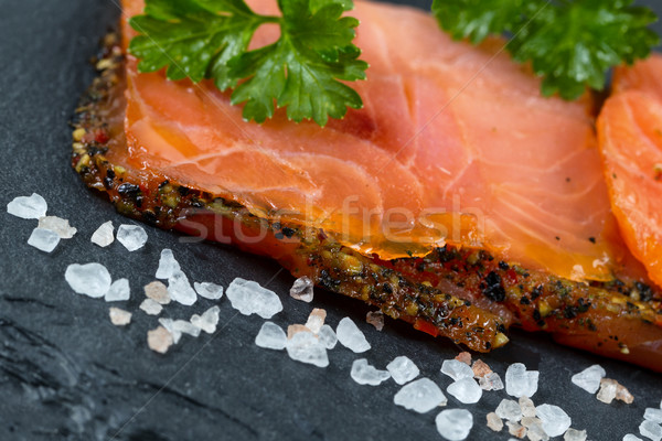 Smoked salmon slices and seasoning on natural black stone backgr Stock photo © tab62