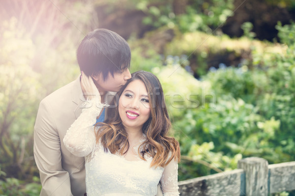 Expecting mom receiving kiss from her husband while outdoors Stock photo © tab62