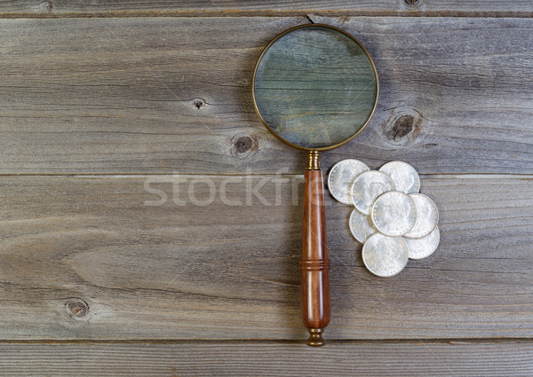 Silver dollar coin collection and round vintage magnify glass on Stock photo © tab62